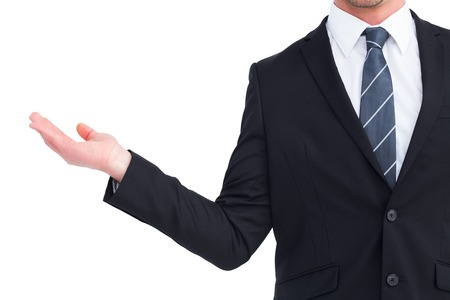 hand out: Businessman holding his hand out on white background
