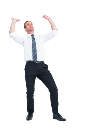 wincing: Businessman bending and pushing on white background Stock Photo