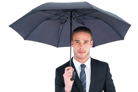 sheltering: Unsmiling businessman sheltering under umbrella on white background