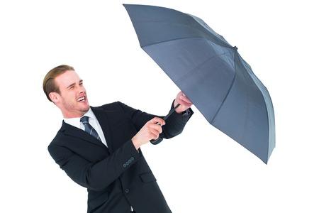 sheltering: Businessman holding umbrella to protect himself on white background