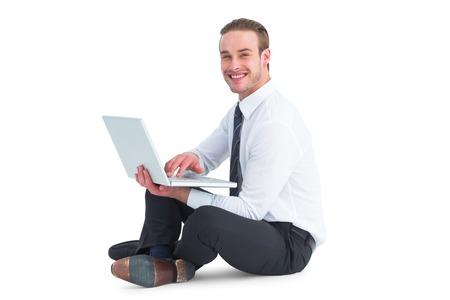Happy businessman sitting and using laptop on white background photo