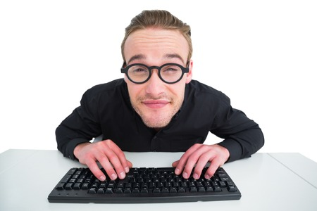 Smiling businessman typing on keyboard at desk on white background photo