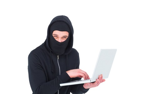 to steal: Hacker in balaclava using laptop to steal identity on white background