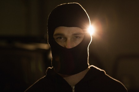 shadowy: Criminal in balaclava looking at camera in a shadowy setting