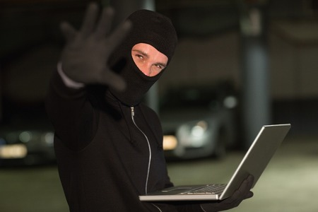 shadowy: Hacker in balaclava gesturing and using laptop on shadowy background