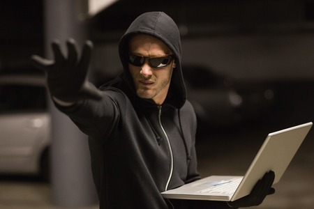 stolen identity: Hacker in balaclava gesturing and using laptop on shadowy background