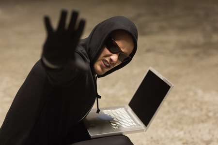 stolen identity: Frowning hacker in sunglasses gesturing on white background Stock Photo