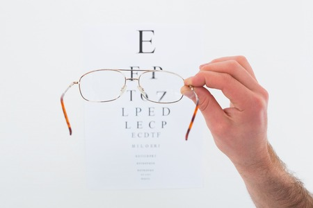auscultation: Hand holding glasses for a eye test on white background