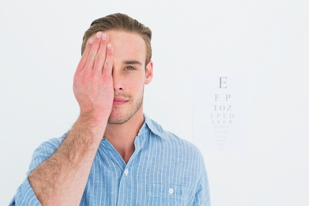 sense of sight: Unsmiling patient looking at camera with one eye on white background