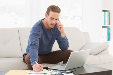 Serious man paying his bills on laptop at home in the living room photo
