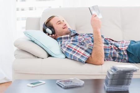 relajado: Relajado hombre escuchar m�sica tumbado en el sof� en casa, en la sala de estar Foto de archivo