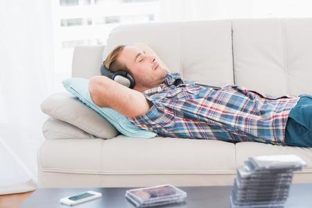 relajado: El hombre durmiendo la siesta en el sof� con la m�sica en su casa en la sala de estar