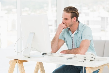 Concentrated businessman working with computer in his office photo