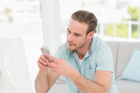 text messaging: Cheerful businessman text messaging in his office Stock Photo