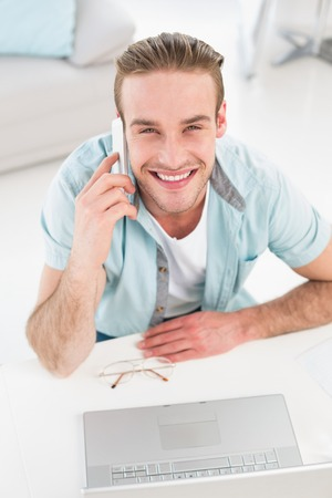 Happy casual businessman on the phone in the office photo