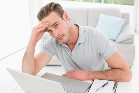 apprehensive: Anxious businessman using laptop and notebook in his office