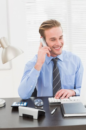 phoning: Smiling businessman working and phoning at his desk in his office