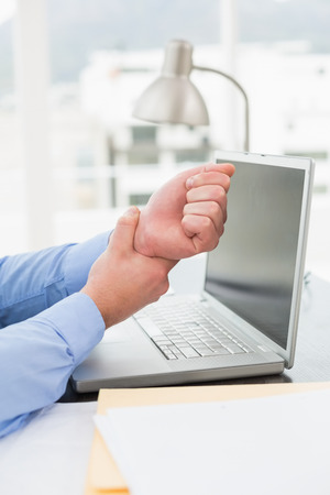 wrist pain: Businessman suffering from wrist pain in his office