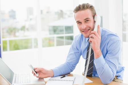 text messaging: Businessman on the phone while text messaging in his office