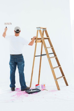 step ladder: Full length rear view of man painting by step ladder on white background
