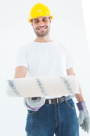 redecorating: Happy man wearing helmet while using paint roller on white background