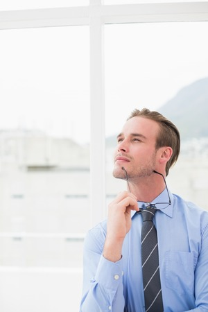 day dreaming: Businessman holding glasses in day dreaming in his office