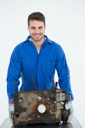Portrait of smiling young male machanic carrying old car engine on white background photo