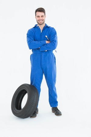 mechanician: Full length portrait of smiling young male mechanic with arms crossed standing by tire on white background Stock Photo