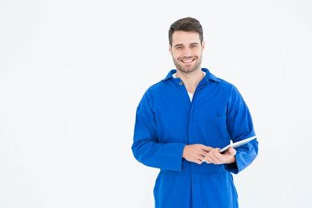 Portret van gelukkige jonge man monteur met behulp van digitale tablet op een witte achtergrond