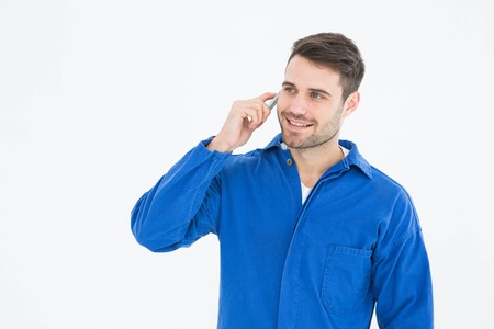 mechanician: Happy young male mechanic using mobile phone on white background