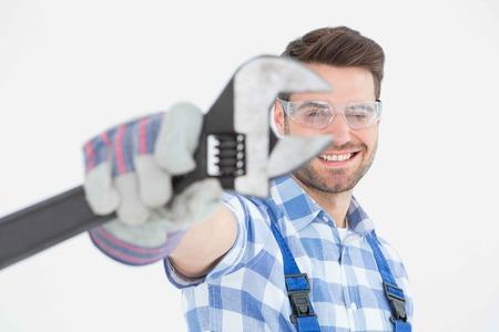 fontanero: Retrato de manitas conf�a en el uso de gafas de protecci�n mientras sostiene la llave en el fondo blanco