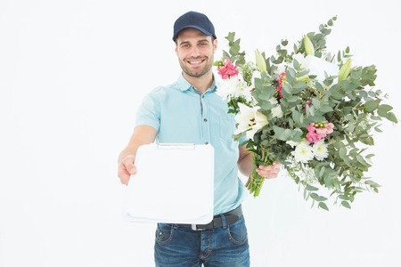 Portrait of happy flower delivery man showing clipboard on white background