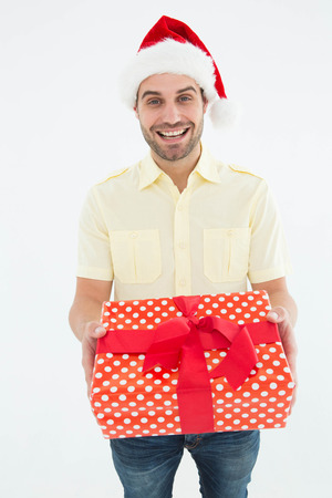 wearing santa hat: Portrait of smiling man wearing Santa hat while holding gift on white background