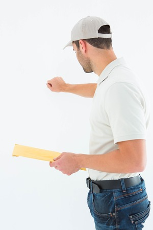 knocking: Side view of delivery man with envelop knocking on white background