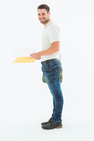 envelops: Side view portrait of smiling derivery man with envelops on white background