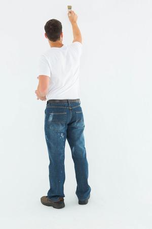 hombre pintando: Vista posterior de cuerpo entero de la pintura del hombre en el fondo blanco