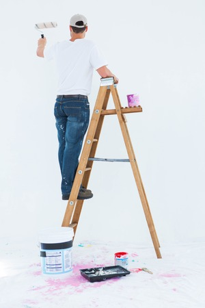 climbing ladder: Full length rear view of man on ladder painting with roller over white background