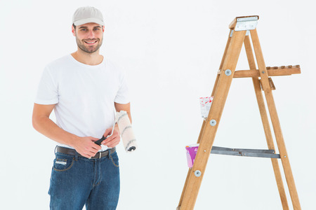 redecorating: Portrait of smiling man holding paint roller while standing by ladder on white background Stock Photo