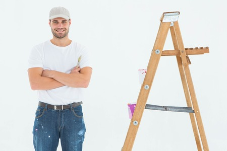 redecorating: Portrait of happy man holding paintbrush while standing by ladder on white background