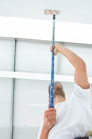 hombre pintando: �ngulo de visi�n baja del hombre que pinta el techo de su casa