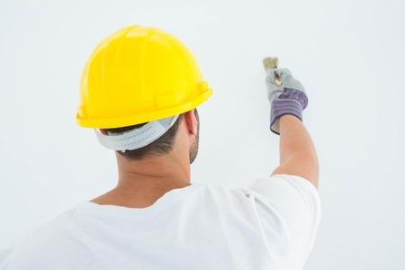 redecorating: Rear view of man wearing hard hat while using paintbrush on white background
