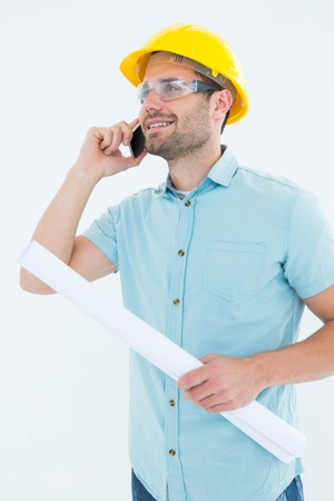 Happy male architect with blueprint talking on mobile phone over white background photo