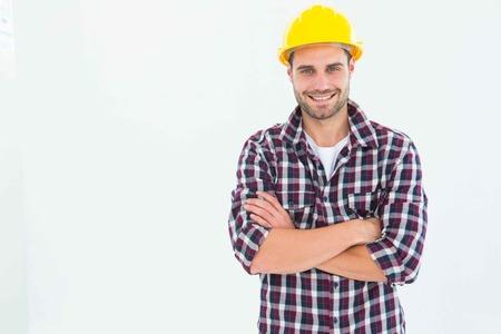 handome: Portrait of handome male repairman standing arms crossed on white background