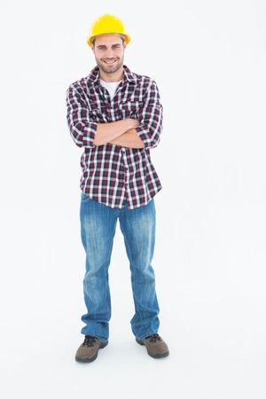 handome: Full length portrait of handome male handyman standing arms crossed on white background
