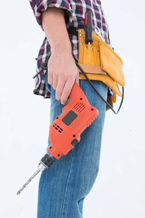 Side view of male handyman holding drill machine over white background photo