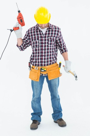 Full length of male repairman holding drill machine and hammer on white background photo