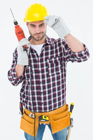 Portrait of confident handyman holding drill machine on white background photo