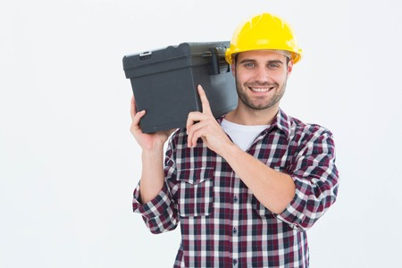 shoulder carrying: Portrait of happy male repairman carrying toolbox on shoulder over white background Stock Photo