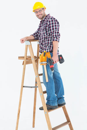 power drill: Full length portrait of repairman climbing ladder while holding power drill on white background Stock Photo