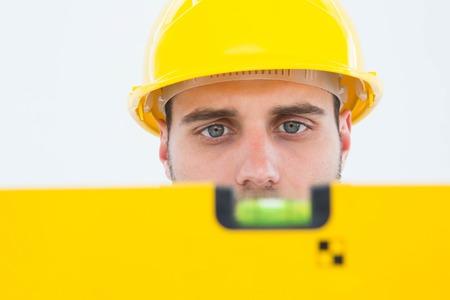 Close-up of male technician using spirit level on white background photo